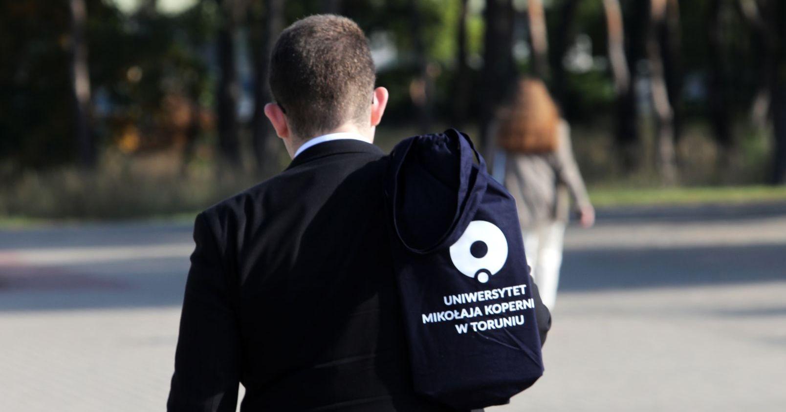 Człowiek z torbą z logo UMK
